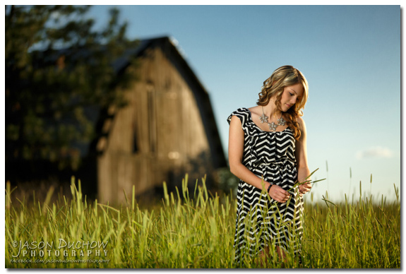 senior portrait in a field with an old barn