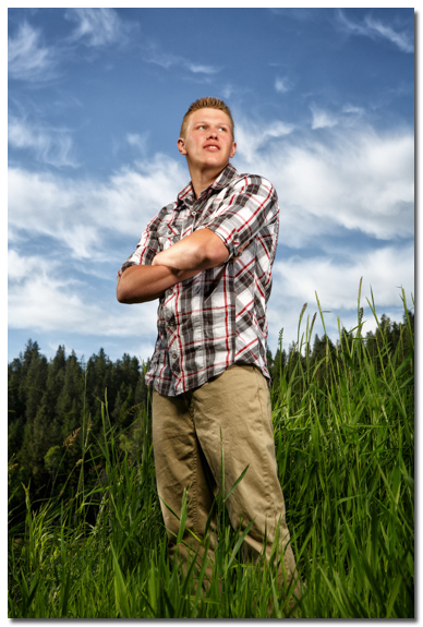 senior portrait with blue sky and clouds