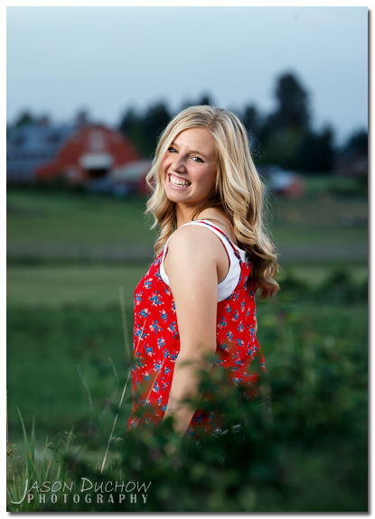 senior portrait with a barn in the distance