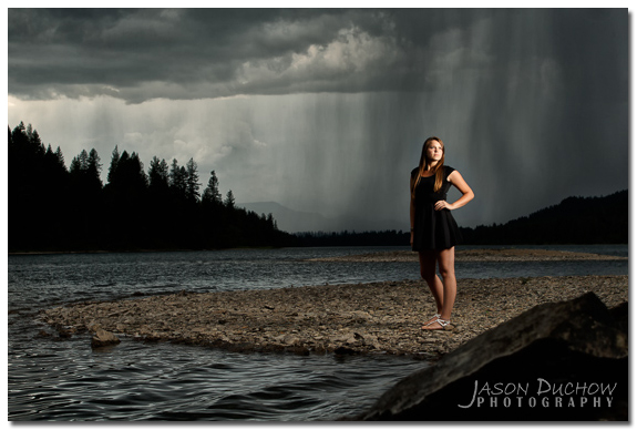senior portrait with dramatic clouds and rain in the distance